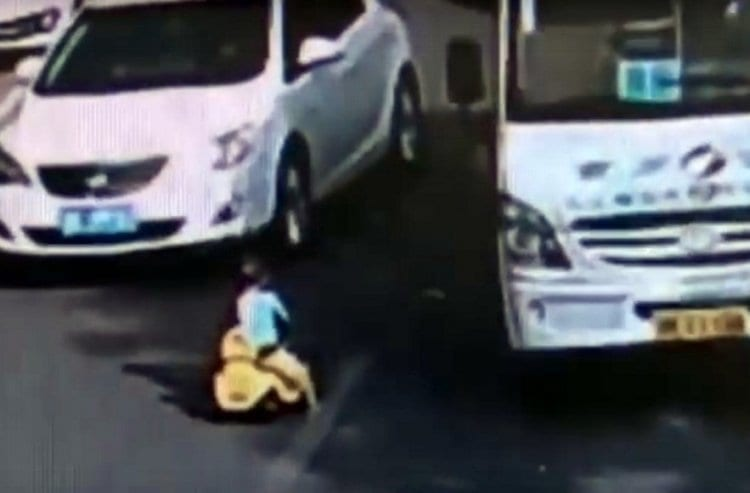 Photo of Disturbing Documentation: Toddler Riding a Tricycle in the Middle of a Busy Road